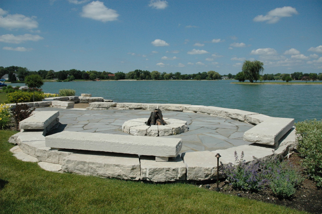 Stone Firepit On The Water With Stone Patio And Outcropping Seating