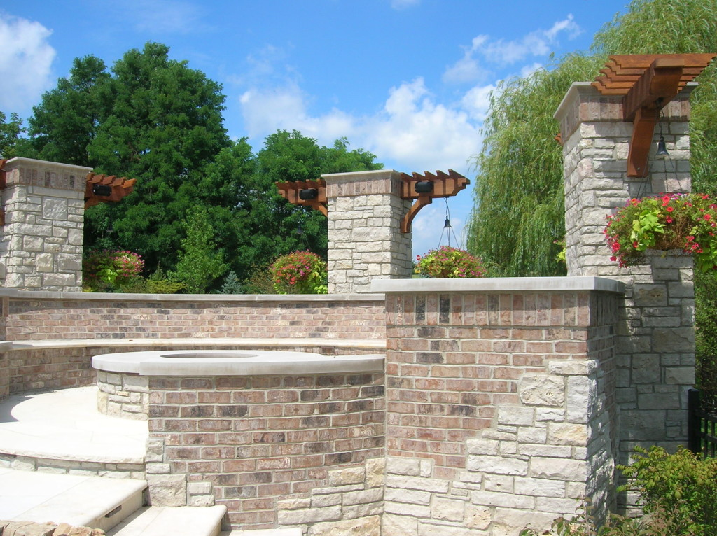 Brick and natural stone firepit with seatwalls, columns and custom cedar accents